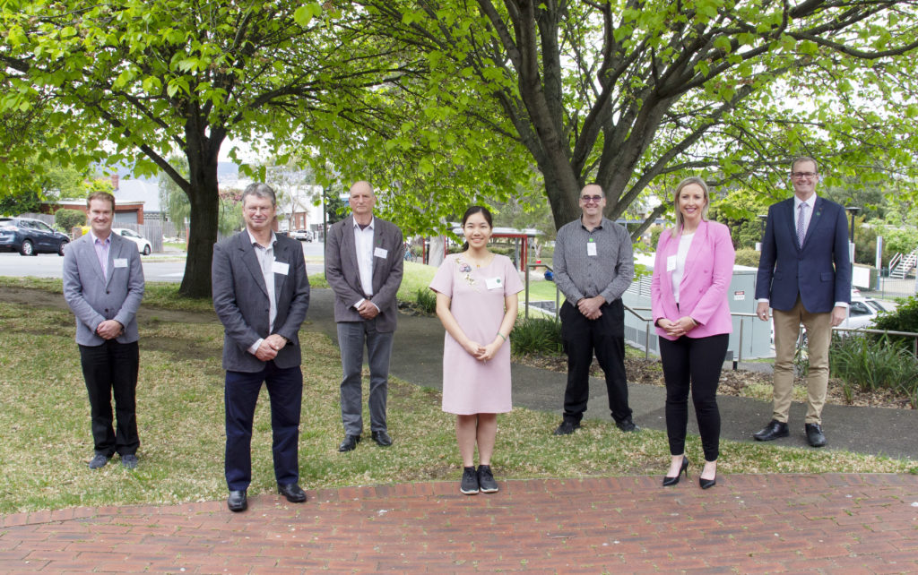 A mixed group of professionally dressed people stand socially distanced outside with nice trees in background.