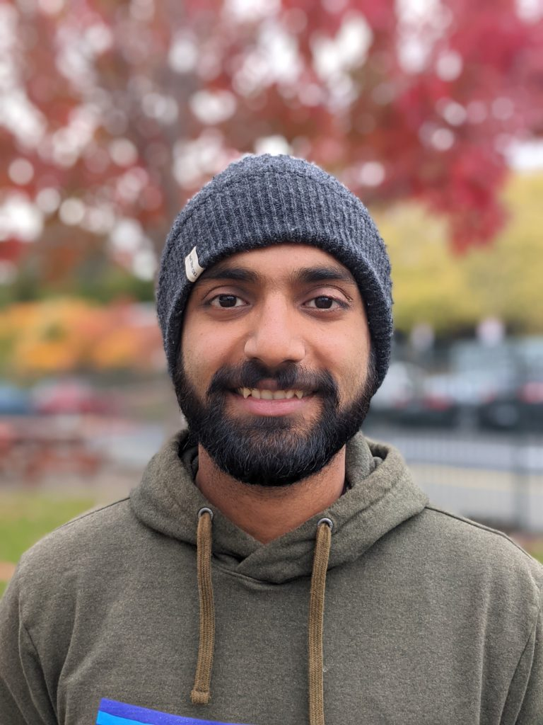 A man standing outside in autumn smiles. He is wearing a beanie, hoodie, and has a beard